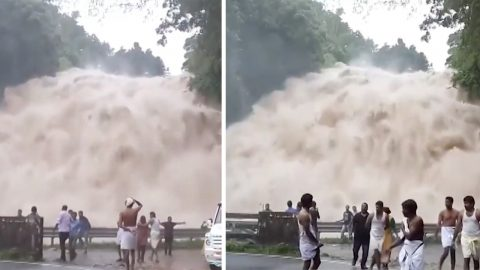 Flooded river creates powerful waterfall right next to busy road Image