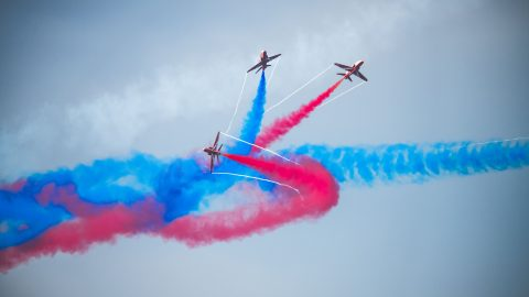 Red arrow jets leave vibrant colour trails against moody grey sky Image