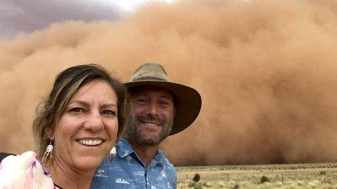 Family pull over to watch tsunami of orange dust approach their car during impressive storm Image