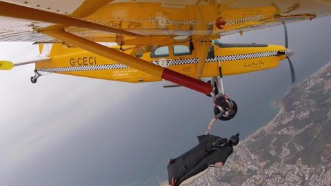Now That Is An Inflight Snack! Wingsuit Pilot Passes Banana To Plane Passenger Hanging Out Of Door In Mid-flight Image