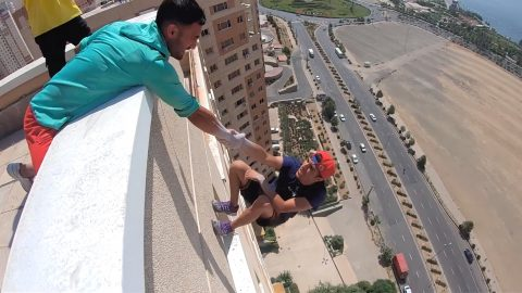Heart-stopping moment daredevil lets go of his friend's hand while hanging off a building – before grabbing on again Image