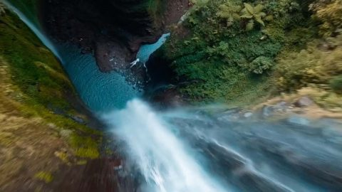 DRONE FLIES THROUGH SPECTACULAR WATERFALL IN JUNGLE CANYON Image