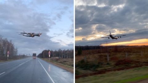 LARGE LOW-FLYING PLANE GOES RIGHT OVER THE TOPS OF MOVING CARS Image