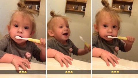 Cheeky girl pretends shes using electric toothbrush Image