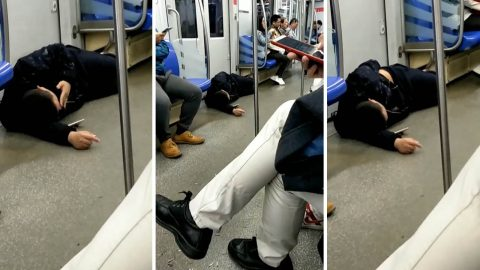 Bizarre video shows man lying down on dirty subway train floor so he can watch his phone Image