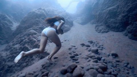 Freediver carries heavy rock across ocean floor while holding breath Image