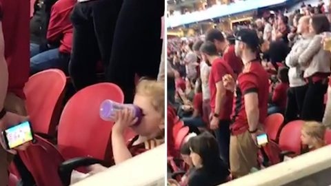 World's best dad? Football fan holds mobile phone behind his back so daughter can watch cartoons  Image