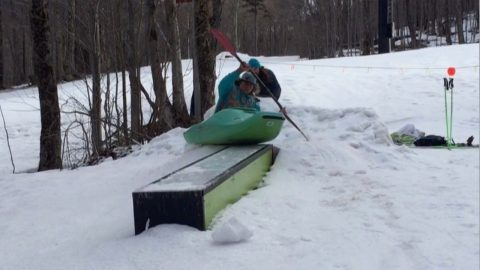 Crafty Kayaker Does Spinning Trick On Snowboard Grind Image