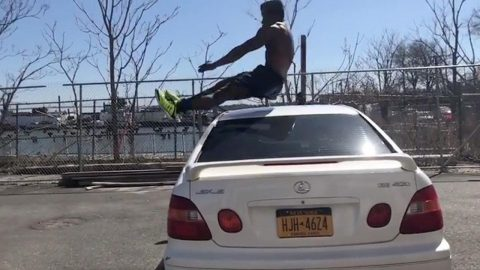 Talented Athlete Displays Formidable Agility By Leaping Over People And Cars Image