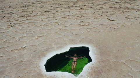 TRAVELLER SWIMS IN STUNNING NATURAL POOL IN THE MIDDLE OF SALT DESERT Image