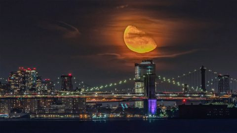 PHOTOGRAPHER CAPTURES STUNNING MOMENT HUNTERS MOON RISES OVER NEW YORK CITY Image