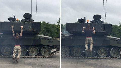 PERSONAL TRAINER PROVES HE'S A REAL TANK BY DOING PULL UPS ON MOVING ARMY VEHICLE Image