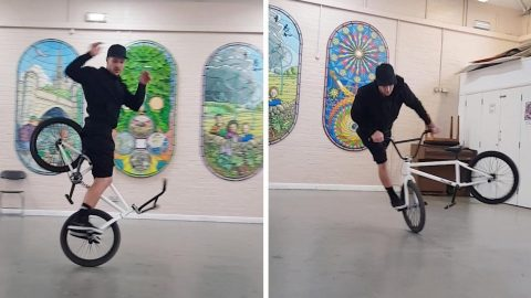 TALENTED BMX RIDER PERFORMS STUNTS WHILE STANDING ON FRONT WHEEL Image