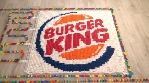 SATISFYING CLIPS SHOWS 25,000 DOMINOS FALL IN THE PATTERN OF FAMOUS FAST FOOD LOGOS Image
