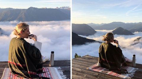 TEA FOR TWO: COUPLE SHARE CUP OF TEA IN CLOUDS WITH STUNNING VIEWS OF AUSTRIAN MOUNTAIN RANGE Image