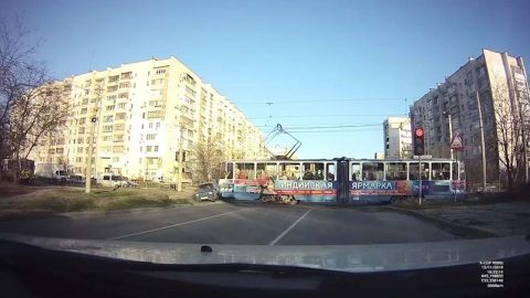 IMPATIENT DRIVER WHO CUT ACROSS MOVING TRAM GETS INSTANT KARMA AS THE TRAIN CAN'T HELP BUT CRASH INTO THE SIDE Image