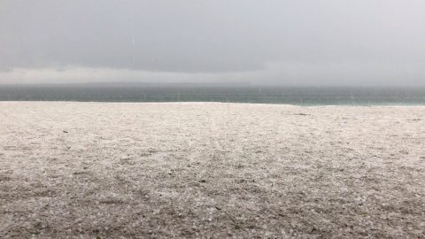 EXTREME HAIL STORM HITS SANDY BEACH IN AUSTRALIA COVERING THE SHORELINE IN A WHITE BLANKET Image
