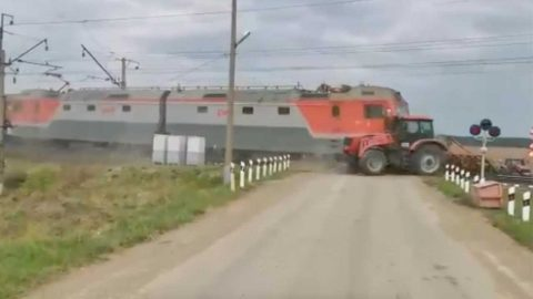 TRAIN PLOWS INTO TRACTOR STUCK ON TRACKS IN DRAMATIC VIDEO Image